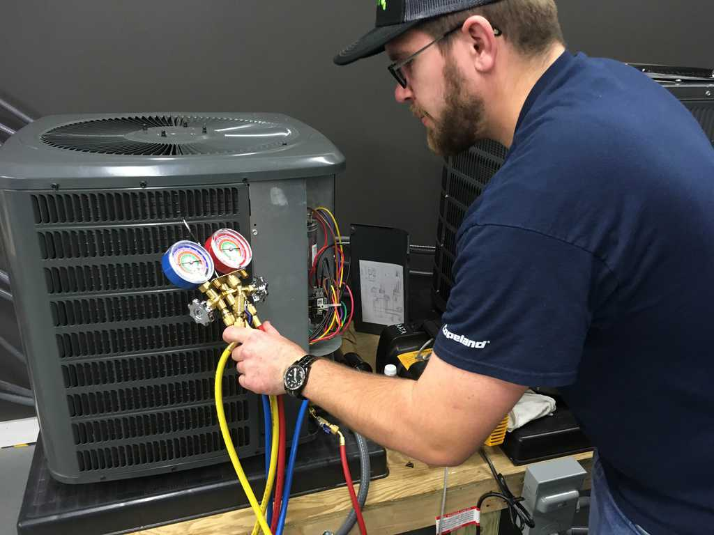 HVAC student training on an AC Unit