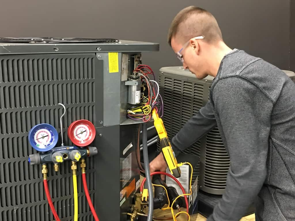 HVAC student working on an air conditioner